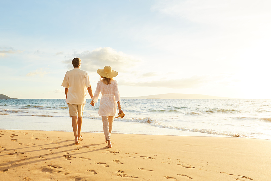Couple Walking on Beach not thinking about Retirement Planning